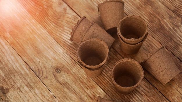 Puste doniczki torfowe dla sadzonek na drewnianym tle. prace ogrodowe. koncepcja przygotowania narzędzi ogrodniczych do wiosennego sadzenia roślin i kwiatów