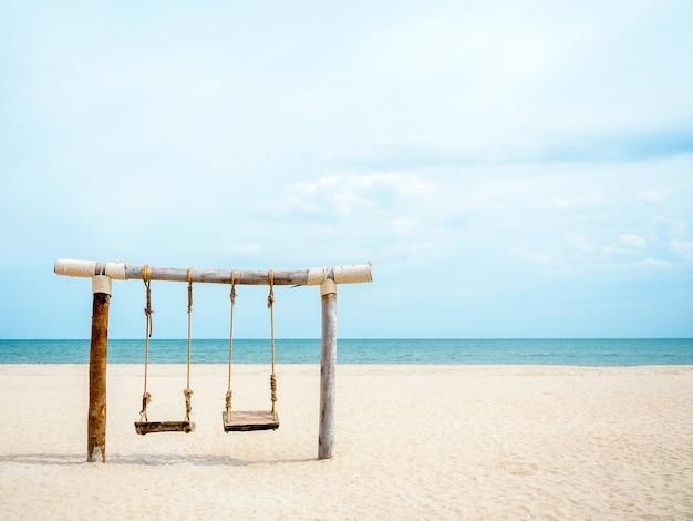 Puste drewniane bliźniacze siedzenie huśtawka na plaży, na morze, piasek, morze i błękitne niebo