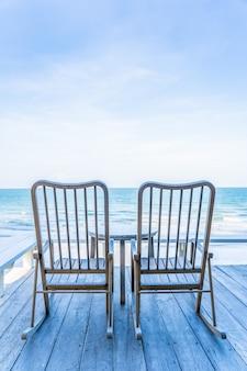 Puste drewniane krzesło i stół na odkrytym patio z pięknej tropikalnej plaży i morza