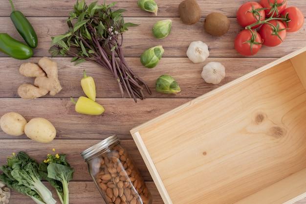 Puste drewniane pudełko na dostawę bezpłatnego sklepu spożywczego ze świeżych produktów warzywnych w tle