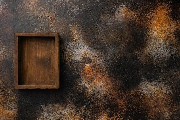 Puste drewniane pudełko z kopią miejsca na tekst lub jedzenie, widok z góry płasko leżał, na starym ciemnym tle rustykalnym stołu