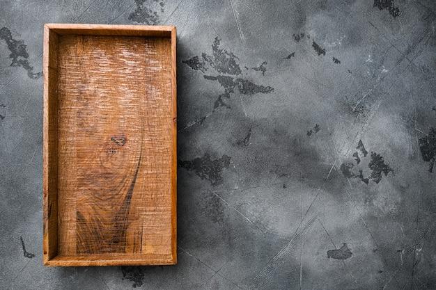 Puste drewniane pudełko z kopią miejsca na tekst lub jedzenie, widok z góry płasko leżał, na szarym tle kamiennego stołu