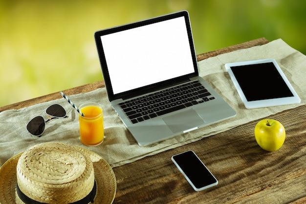 Puste ekrany laptopa i smartfona na drewnianym stole na zewnątrz z naturą na ścianie, makiety.
