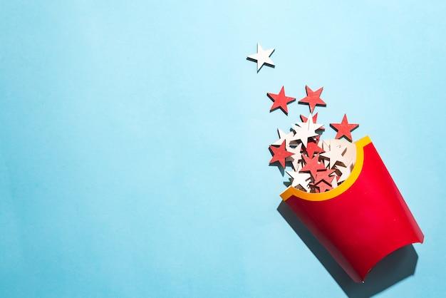 Puste frytki z kolorowe drewniane sylwestrowe gwiazdki na niebieskim tle papieru