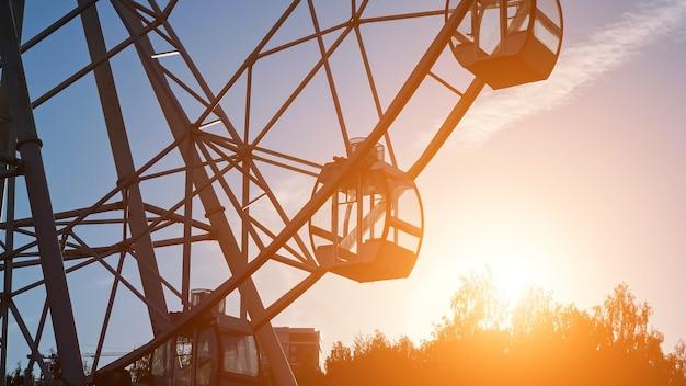 Puste kabiny dużych operacyjnych metalowych przejażdżek diabelskim młynem obracają się w lokalnym parku przed niebem nad sylwetkami drzew wieczorem po zachodzie słońca