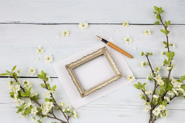 Puste kartki papieru, stara ramka na zdjęcia, wieczne pióro i wiśniowe kwiaty
