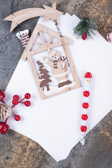 Puste kartki papieru z dekoracjami świątecznymi na marmurowej przestrzeni.
