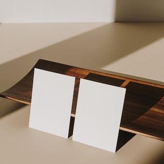Puste kartki papieru z drewnianą tacą z cieniem światła słonecznego na beżowym tle. minimalny szablon marki biznesowej