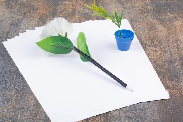Puste kartki papieru z piórem na marmurowej przestrzeni.