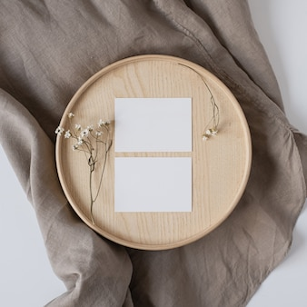 Puste kartki papieru z suchymi kwiatami na drewnianej trumnie i szarym lnianym kocu