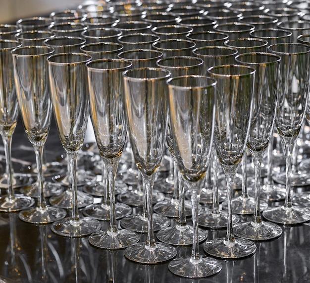 Puste kieliszki do szampana stojące w rzędzie. wiele kieliszków do szampana