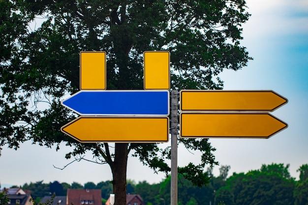 Puste kierunkowe znaki drogowe przed parkiem. metalowe strzałki na drogowskazie.