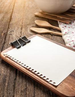 Puste klip menu arkusz papieru i łyżka na rustykalne drewniane
