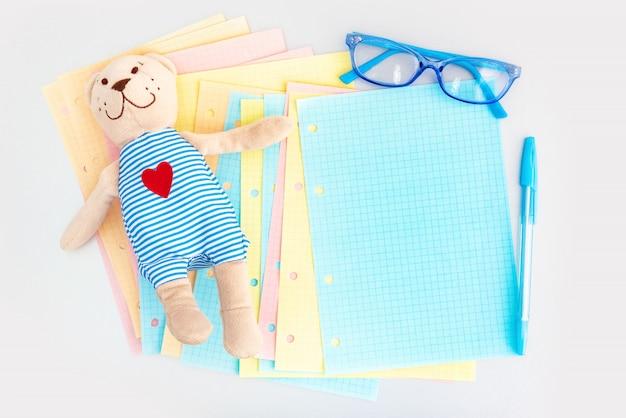 Puste kolorowe strony, zabawki i szklanki dla dzieci na srebrnym biurku