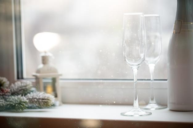 Puste kryształowe kieliszki i butelka szampana przed oknem koncepcja nowego roku
