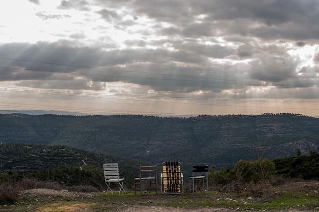 Puste krzesła w górach pod ciemnym zachmurzonym niebem