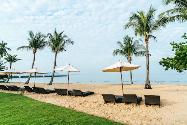 Puste krzesło plażowe z palmą na plaży z morzem