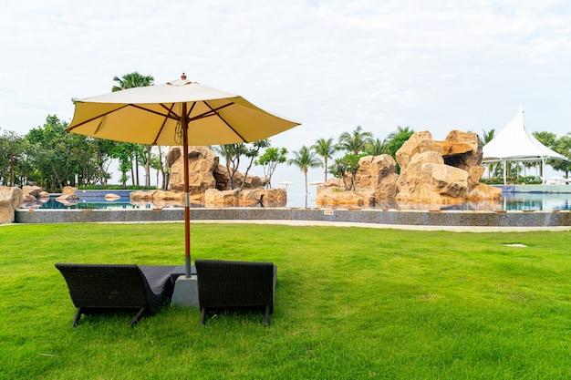 Puste krzesło plażowe z parasolem wokół basenu