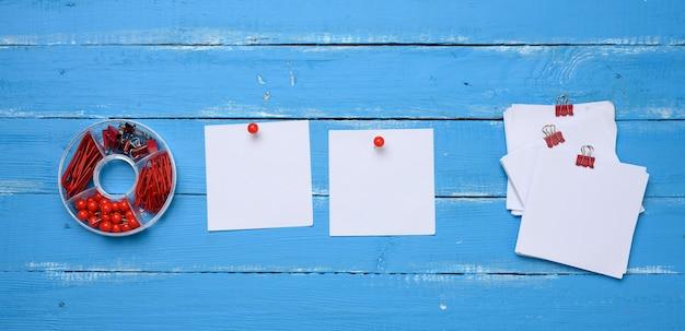 Puste kwadratowe arkusze papieru i zestaw papeterii ze spinaczami do papieru i spinaczami na niebieskim tle drewnianych