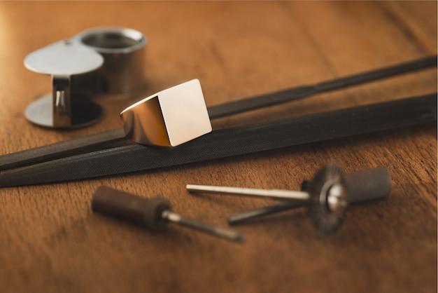Puste logo pierścionek pusty sterling złoty pierścionek sygnet pierścionek inicjałowy i narzędzia jubilerskie na drewnianym anty...