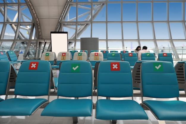 Puste miejsca pasażerskie na lotnisku podczas wybuchu covid19 i puste miejsce na fotelu czerwony krzyż pokazuje unikanie w terminalu lotniska.