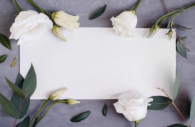 Puste miejsce na papier. rama z kwiatami. jedwabna wstążka. szare tło. prosty bukiet. kartka z życzeniami.