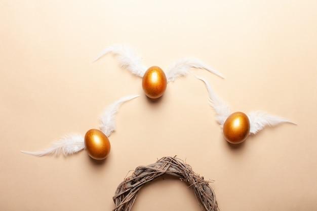 Puste miejsce na tekst, baner wesołych świąt. malowane złote jajka, białe pióra.