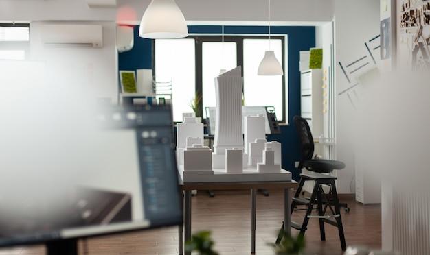 Puste miejsce pracy dla architektonicznego biznesu ze sprzętem jako deska plan papieru zeszyt notatnik spoiwa komputer. pokój z makietą modelu budynku dla nowoczesnych planów projektowych.