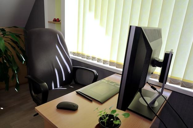 Puste miejsce pracy przy komputerze w pobliżu okna z żaluzjami