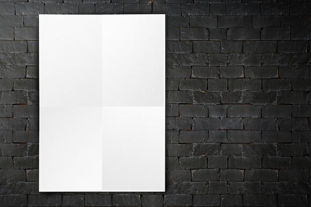 Puste miejsce składający papierowy plakatowy obwieszenie na czarnym ściana z cegieł