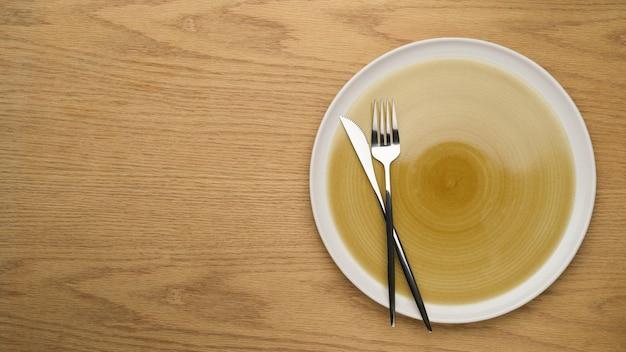 Puste naczynie ceramiczne, makieta talerz ceramiczny, widelec i nóż stołowy na drewnianym stole, widok z góry, czysty talerz, tło ustawienia stołu