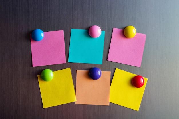 Puste naklejki na notatki na lodówce przymocowane magnesami.