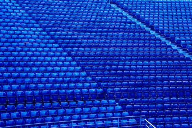 Puste niebieskie siedzenia na stoisku stadionu piłkarskiego.
