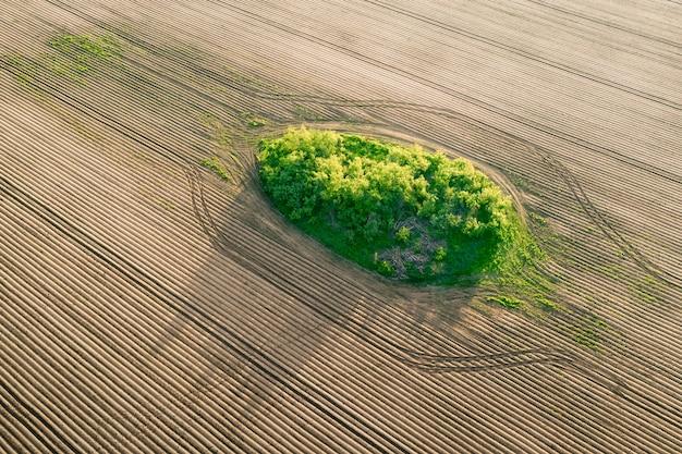 Puste niezasiane pole i zielony trawnik pośrodku widoku z drona
