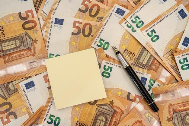 Puste notatki wirh pióra i 50 banknotów euro. koncepcja finansowa i liczenia