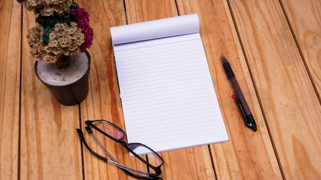 Puste notatki z białego papieru z kwiatem szarotki i okularami na górnym drewnianym stole