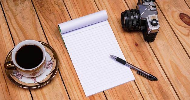 Puste notatki z białej księgi z kawą i starym aparatem na stole z drewna