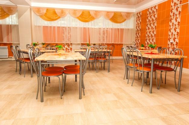 Puste nowe stoliki w dużej szkolnej stołówce