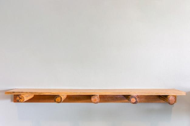 Puste odgórne drewniane półki na bielu cementują ścianę. do wyświetlania produktu