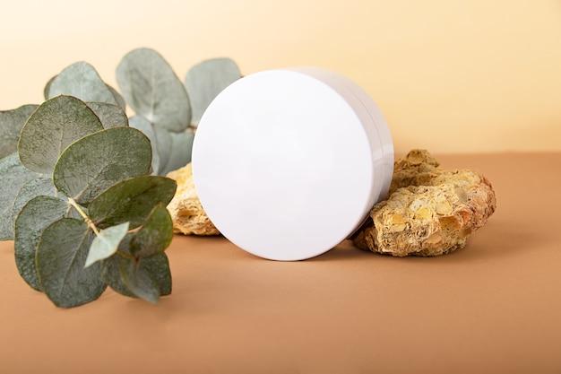 Puste okrągłe pudełko na kosmetykigałąź eukaliptusa i ozdobne kamienie naturalne za