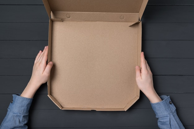 Puste otwarte pudełko pizzy w rękach dzieci. czarne tło. widok z góry. skopiuj miejsce