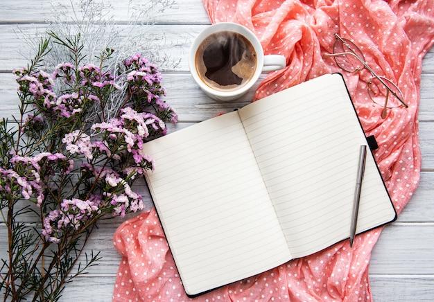Puste otwarty notatnik z kwiatami i filiżanką kawy, widok z góry