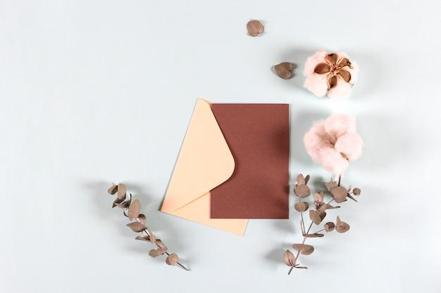 Puste papierowe koperty na zaproszenie z liści eukaliptusa i bawełnianych kwiatów