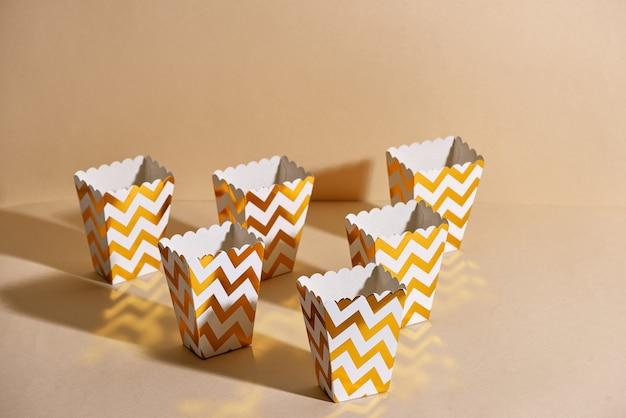 Puste papierowe złote kubki na beżowej powierzchni