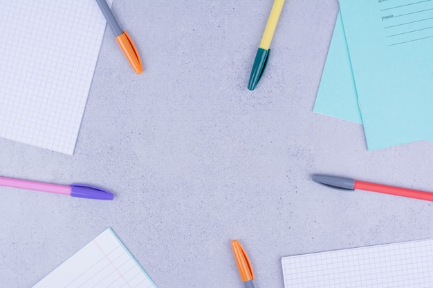 Puste papiery i długopisy na szarym tle.