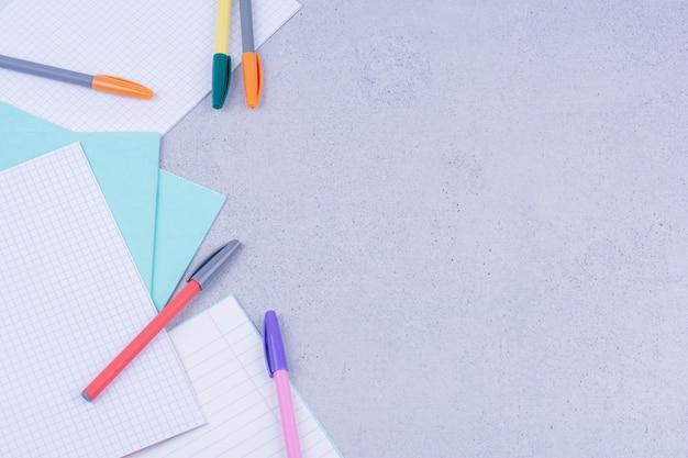 Puste papiery i długopisy wielokolorowe na białym tle na szarej powierzchni