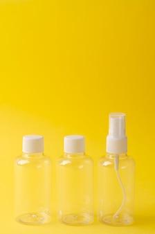 Puste plastikowe butelki na żółtym.