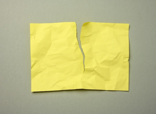 Puste podarte zmięty żółty arkusz papieru na szarym tle, miejsce