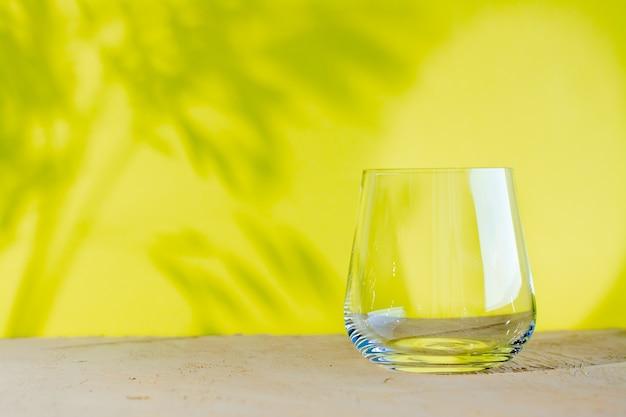 Puste przezroczyste szkło na beżowej powierzchni na żółto z roślinnymi cieniami