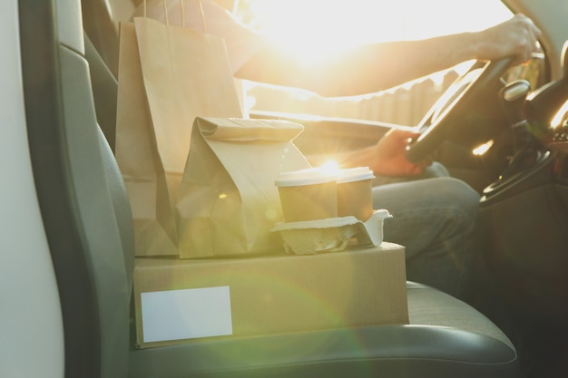 Puste pudełko, filiżanki do kawy, paczki papieru i kurier w samochodzie. dostawa